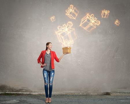 Glückliche junge Frau in der roten Jackenöffnungsgeschenkbox Standard-Bild - 51843314