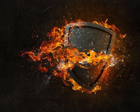 Stone broken shield in fire flames on dark background Stock Photo