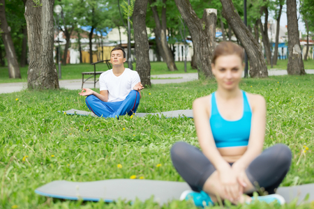 position d amour: Young man and woman practicing yoga in summer park Banque d'images
