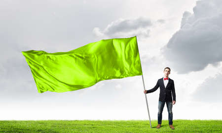windy energy: Young man in bowtie with green waving flag on stick Stock Photo