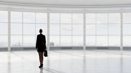 Businesswoman with suitcase in modern interior looking in office window