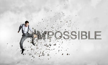 Young emotional man crashing word impossible with hand punch Stock Photo