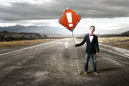 hitch hiker: Young man in jacket and bowtie on road holding sign