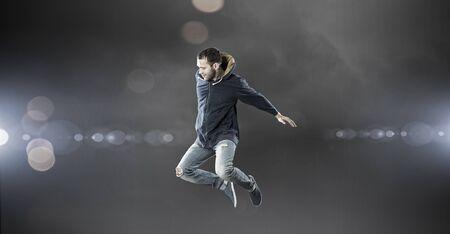 Young dancer man in jump over dark background