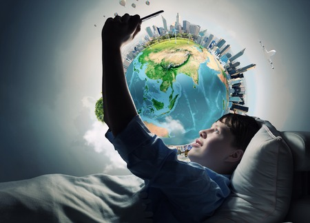 Teenager boy in bed using his tablet pc for entertainment. Elements of this image are furnished by NASA