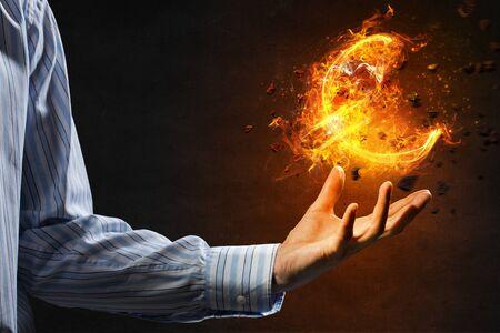 Quema de bola de fuego del símbolo del euro en la mano del hombre de negocios