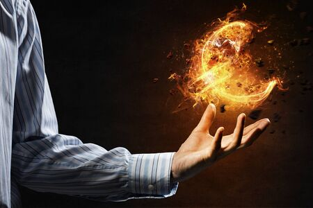 burning money: Burning fire ball of euro sign in businessmans hand Stock Photo