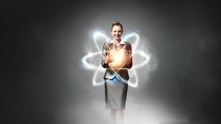 Attractive businesswoman holding glowing atom in hands