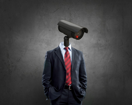 security monitoring: Portrait of camera headed man in suit as security concept