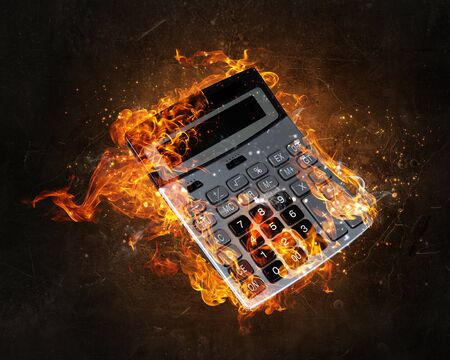 compute: Calculator in fire flames against black background