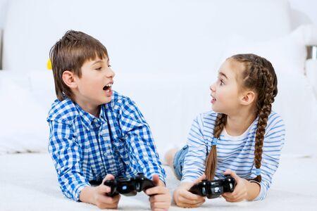Emotional kids lying on floor playing games on joystick 免版税图像