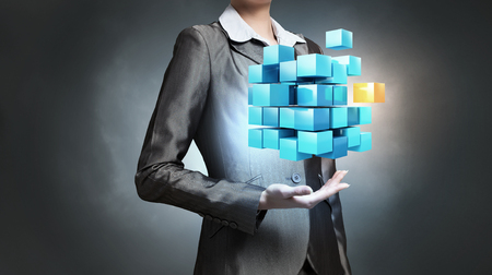 technology concept: Close view of businesswoman shows cube as symbol of modern technology Stock Photo