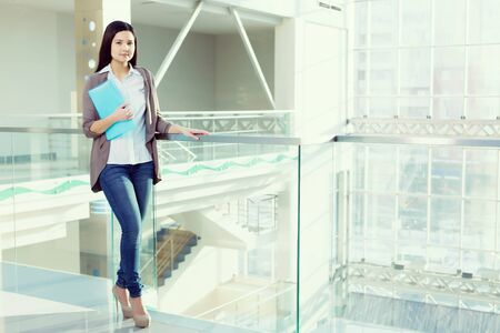 parapet: Young brunette woman in modern glass interior with folder in hands Stock Photo