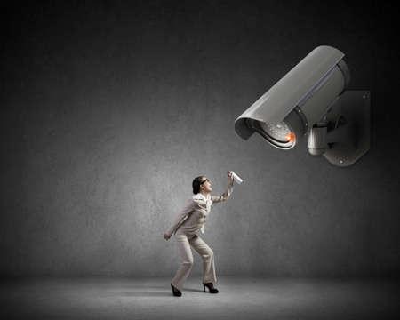 keep an eye on: Young woman spraying aerosol on CCTV camera control Stock Photo