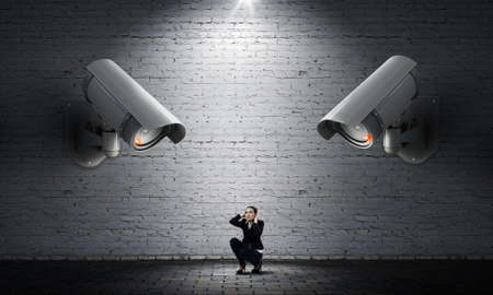 keep an eye on: Young scared woman in room under CCTV camera control Stock Photo