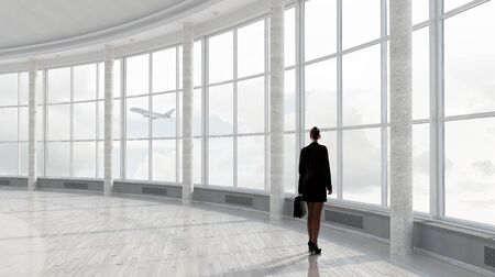 ladies day: Businesswoman with suitcase in modern interior looking in office window