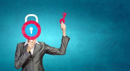 hidden success: Businesswoman hiding her face behind lock card Stock Photo