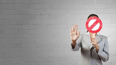 hidden success: Businesswoman hiding her face behind mask and showing stop gesture