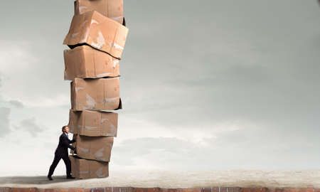 Businessman pushing with effort big stack of carton boxes Stock Photo