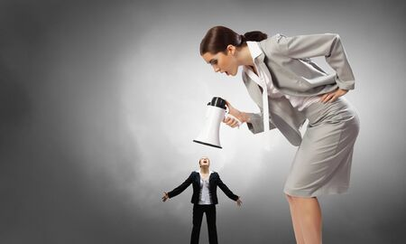 emotionally: Angry woman shouting emotionally in megaphone at little woman