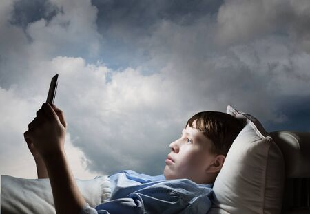 boyhood: Teenager boy in bed using his tablet pc for entertainment