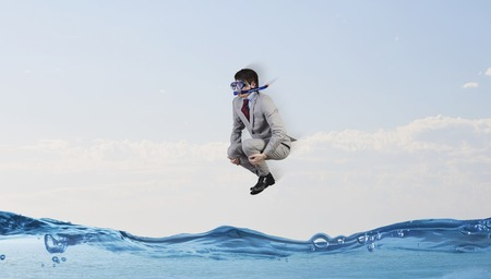 diving: Young businessman in suit and diving mask jumping in water