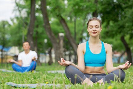 position d amour: Jeune homme et la femme à pratiquer le yoga dans le parc d'été