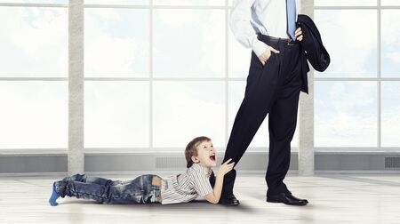 Close up of legs of busy father going to job and his son praying him to stay Stock Photo