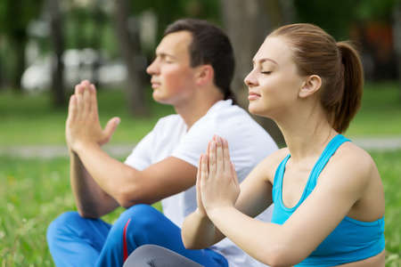 sitting meditation: Young man and woman practicing yoga in summer park Stock Photo