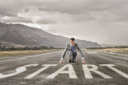 business challenge: Young businessman on road ready to run race Stock Photo