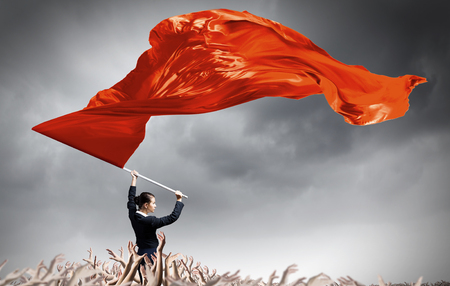 Young determined businesswoman with red flag in hands Foto de archivo