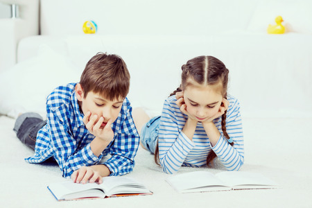 kid reading: School boy and girl laying on the floor and reading book