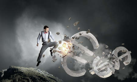 banking problems: Emotional businessman breaking with hand stone euro symbol Stock Photo