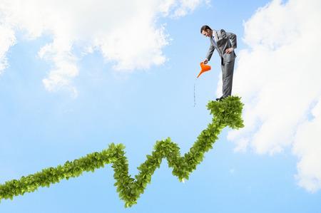 年輕快樂的商人與澆水能綠色增長的曲線圖 版權商用圖片
