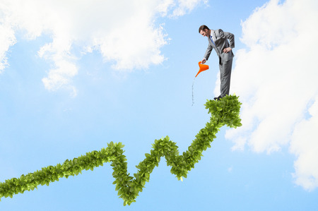 growing business: Young cheerful businessman watering green growing graph with can Stock Photo