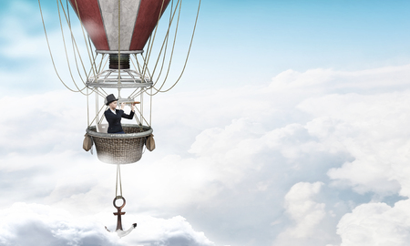 hight: Young businesswoman flying hight in sky in colorful aerostat Stock Photo