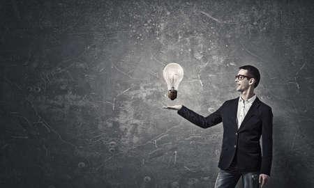 Junger Student Kerl in der Jacke Glühbirne in der Palme zeigt Standard-Bild