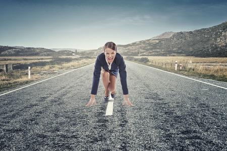 road position: Young determined businesswoman on road standing in start position