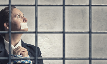 speechless: Young speechless businesswoman in ward with tied hands and adhesive tape on mouth Stock Photo