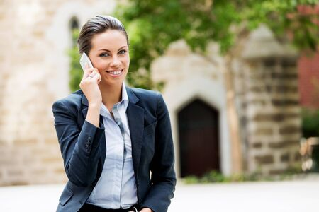phone professional: Portrait of young business woman with mobile phone outdoors