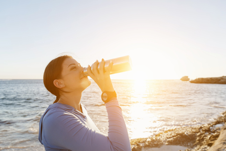 water drink: Young woman drinking water after exercising on beach Stock Photo