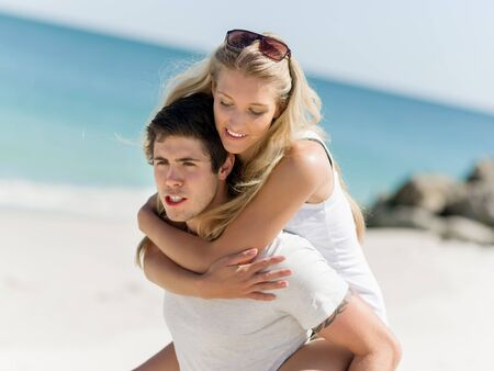 carrying girlfriend: Portrait of man carrying girlfriend on his back on the beach