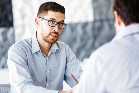 Twee knappe zakenman in kantoor zitten aan de balie en praten Stockfoto
