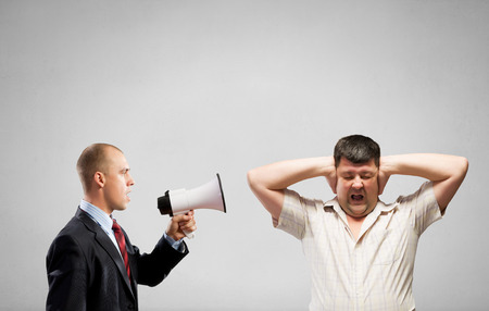 humiliation: Aggressive businessman screaming in megaphone on his colleague