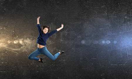 Young woman dancer in jump over dark background