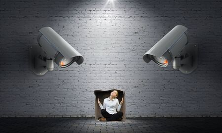 under control: Young scared woman in room under CCTV camera control Stock Photo
