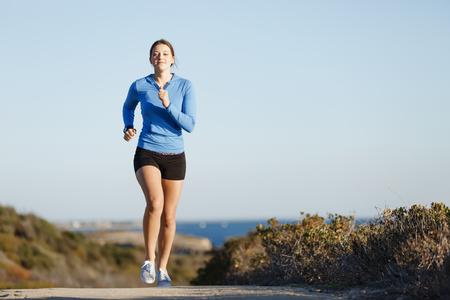 women sport: Fit female fitness model jogging along ocean