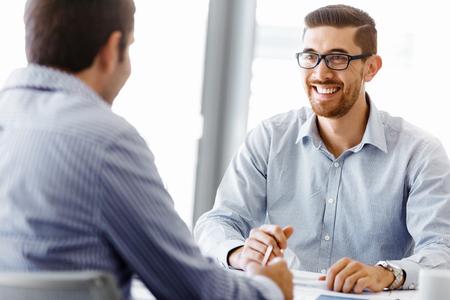 Zwei schöne Geschäftsmann in Büro am Schreibtisch sitzen und sprechen Lizenzfreie Bilder