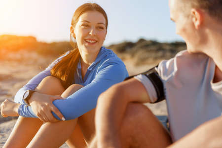 sport wear: Young coulpe in sport wear sitting on beach Stock Photo