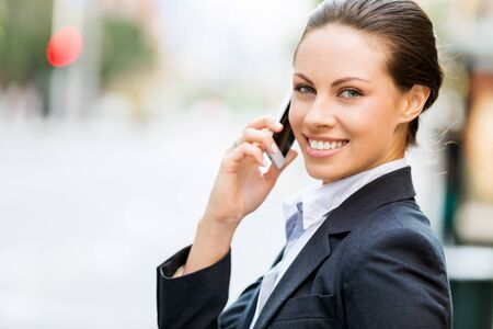 young adults: Portrait of young business woman with mobile phone outdoors